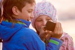 Jonge gelukkige jonge geitjes, jongen en meisjes die, die en smth glimlachen bekijken Stock Afbeelding