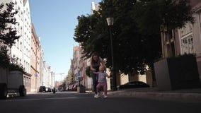 Jonge gelukkige mammalooppas na een kind door een klein meisje onderaan straat het vangen stock video