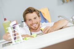 Jonge Gelukkige Mannelijke Portier Cleaning Induction Stove in Keuken royalty-vrije stock afbeeldingen
