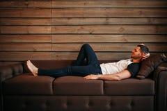 Jonge gelukkige mens die op laag, ontspanning op bank liggen Royalty-vrije Stock Foto's