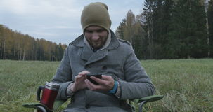 Jonge gelukkige mens die op mobiele telefoon in het park spreken stock videobeelden
