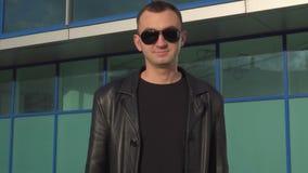 Jonge gelukkige mens in leerjasje en zonnebril die aanbieding goedkeuren door hoofd openlucht te schudden stock video