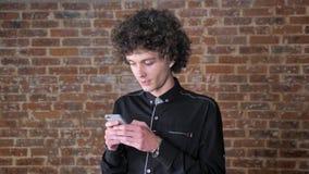Jonge gelukkige mens met krullend op telefoon babbelen en haar die, bakstenen muurachtergrond glimlachen stock footage
