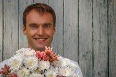 Jonge gelukkige mens met witte bloemen op houten achtergrond Royalty-vrije Stock Foto's