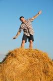 Jonge gelukkige mens op hooiberg Stock Afbeelding