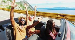 Jonge gelukkige mensen op vakantie die pret het drijven in rode convertibel hebben, gesorteerd stock video