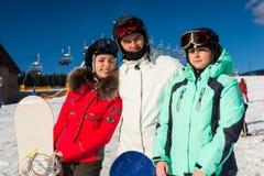 Jonge gelukkige mensen in ski-kostuums en skibeschermende brillen die pret hebben terwijl stock foto's