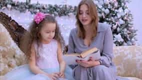 Jonge gelukkige moeder en dochterzitting door de open haard op Kerstnacht die een boek, amid Kerstmislichten lezen en stock video