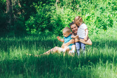 Jonge gelukkige moeder met twee kinderen op gras Stock Afbeeldingen