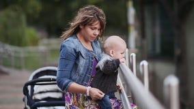 Jonge gelukkige moeder met weinig baby op de brug in het park Geniet van de schoonheid van aard stock videobeelden