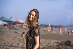 Jonge gelukkige mooie en betoverende blonde vrouw die zoals bij het strand draagt modieuze kleding stellen die vrolijk vers gevoe stock foto's