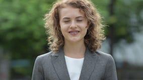 Jonge gelukkige mooie onderneemster die met krullend blond haar in openlucht glimlachen stock videobeelden
