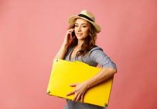 Jonge gelukkige mooie vrouw die in hoed gele koffer en t houden stock foto