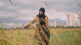 Jonge gelukkige moslimvrouw in hijab die door tarwegebied lopen en, stad met wolkenkrabber op achtergrond glimlachen stock footage