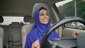 Jonge gelukkige moslimvrouw in hijabzitting achter zelf-drijft stuurwiel van autonome automatische piloot driverless auto stock video