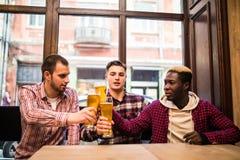 Jonge gelukkige multiraciale mensenvrienden die bier drinken en in bar spreken stock afbeelding