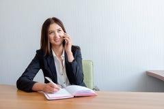 Jonge gelukkige onderneemster die op de telefoon en het schrijven nota's in bureau spreken royalty-vrije stock foto's
