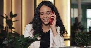 Jonge gelukkige onderneemster die op de telefoon spreken terwijl het zitten in koffie Zij glimlacht Mooi meisje die toevallig heb stock video