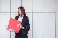 Jonge gelukkige onderneemster die rode omslag houden en voor portret op bureau stellen, het glimlachen royalty-vrije stock foto