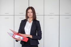 Jonge gelukkige onderneemster die rode omslag houden en voor portret op bureau stellen, het glimlachen stock foto