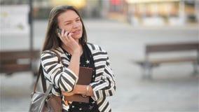 Jonge gelukkige opgewekte lachende vrouw die op mobiele telefoon en meisjesgolven haar hand spreken bij de straat, stads stedelij stock footage