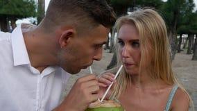 Jonge gelukkige paarzitting in park het spreken lachend en drinkend een kokosnoot Romantisch concept HD, 1920x1080 stock footage