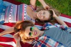 Jonge gelukkige patriotvrouwen op de vlag van Verenigde Staten stock foto