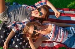 Jonge gelukkige patriotvrouwen op de vlag van Verenigde Staten royalty-vrije stock foto