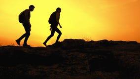 Jonge Gelukkige Reizigers die met Rugzakken op Rocky Trail bij de Zomerzonsondergang wandelen Familiereis en Avonturenconcept stock videobeelden