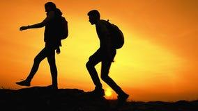 Jonge Gelukkige Reizigers die met Rugzakken op Rocky Trail bij de Zomerzonsondergang wandelen Familiereis en Avonturenconcept stock footage