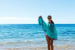 Jonge gelukkige slanke mooie vrouw op het strand, speels, dansend, in werking stellend en hebbend pret in de zomervakantie stock foto
