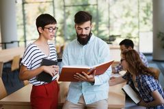Jonge gelukkige studenten die in bibliotheek zitten royalty-vrije stock afbeelding