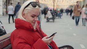 Jonge gelukkige tiener gebruikend telefoon en hebbend pret in de lentepark Het portretstudent van de blonde gelukkige modelvrouw  stock videobeelden