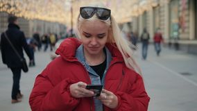 Jonge gelukkige tiener gebruikend telefoon en hebbend pret in de lentepark Het portretstudent van de blonde gelukkige modelvrouw  stock video