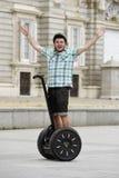 Jonge gelukkige toeristenmens die het hoofddeksel van de veiligheidshelm het berijden stadsreis het segway gelukkig drijven drage Stock Afbeelding