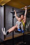 Jonge gelukkige vader die trekkracht UPS op de bar met zoon op zijn benen doen bij de dwars geschikte gymnastiek tegen bakstenen  stock afbeelding