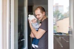 Jonge gelukkige vader die zijn pasgeboren baby op balkon houden Stock Foto