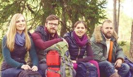 Jonge gelukkige vrienden die op een boomlogin bos en het genieten zitten van Stock Afbeeldingen