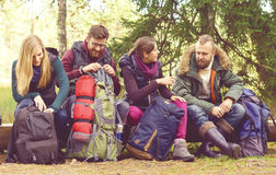 Jonge gelukkige vrienden die op een boomlogin bos en het genieten zitten van Stock Afbeelding