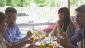 Jonge gelukkige vrienden die van een diner genieten en uit in restaurant hangen stock afbeelding