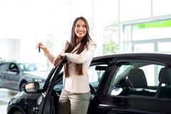 Jonge gelukkige vrouw dichtbij de auto met in hand sleutels - het kopen nieuwe auto royalty-vrije stock foto's
