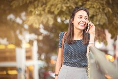 Jonge, gelukkige vrouw die aan een celtelefoongesprek luisteren stock fotografie