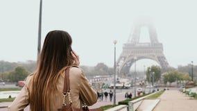 Jonge gelukkige vrouw die binnen de stad in van Parijs, Frankrijk dichtbij de toren van Eiffel lopen en het spreken op mobiele te stock video