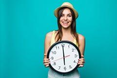 Jonge gelukkige vrouw die een klok met klok 12 op een groene achtergrond houden Portret van positieve vrij jonge vrouw met bij mu Stock Afbeeldingen