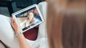 Jonge gelukkige vrouw die een videochat met haar vriend op digitale tablet hebben stock footage