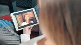 Jonge gelukkige vrouw die een videochat met haar vriend op digitale tablet hebben stock videobeelden