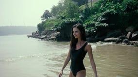 Jonge gelukkige vrouw die en op het strand, gelukkige sexy toerist dichtbij oceaan stellen lopen stock footage