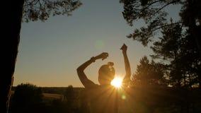 Jonge gelukkige vrouw die en pret in park hebben bij zonsondergang dansen stock footage