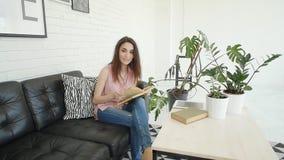 Jonge gelukkige vrouw die in modern binnenland een boek thuis lezen stock video