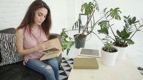 Jonge gelukkige vrouw die in modern binnenland een boek thuis lezen stock footage